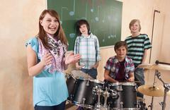 Stock Photo of Germany, Emmering, Girl smiling with boys in background playing drum, portrait