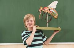 Germany, Emmering, Boy(12-13) holding and fly model, smiling, portrait - stock photo