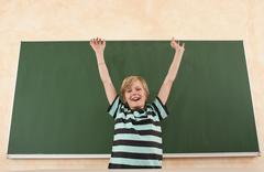 Germany, Emmering, Boy (12-13) smiling with arms up, portrait - stock photo