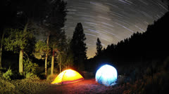 Time lapse star trail streaks over two lite tents in Big Meadow in Sequoia Stock Footage