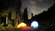 Stock Video Footage of Time lapse star trail streaks over two lite tents in Big Meadow in Sequoia