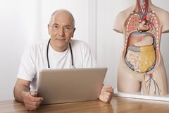 Germany, Munich, Doctor with laptop and human body figurine - stock photo
