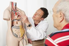 Germany, Munich, Doctor explaining patient human body, smiling - stock photo