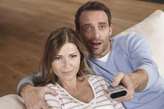 Germany, Couple sitting on couch with man holding remote control, portrait - stock photo
