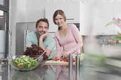 Germany, Couple preparing salad in kitchen, smiling, portrait Stock Photos