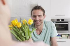 Germany, Woman giving bunch of flowers to man - stock photo