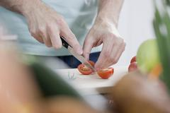 Germany, Mid section of man cutting tomato, close up - stock photo