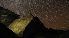 Time lapse star trail streaks over a sacred Owens Valley Paiute petroglyph site Stock Footage