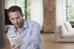 Germany, Man reading book, close up Stock Photos