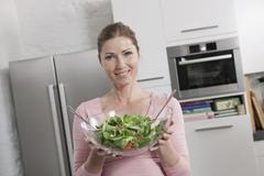 Germany, Woman standing with bowl of salad, portrait, smiling Stock Photos