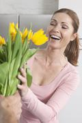 Germany, Woman looking at flowers and smiling - stock photo