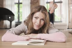 Germany, Woman lying and reading book, smiling, portrait Stock Photos