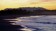 Time lapse of wave breaking along San Buenaventura Beach at sunrise in Ventura, Stock Footage