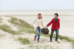Germany, St.Peter-Ording, North Sea, Couple holding picnic basket walking on Stock Photos