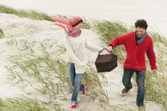 Stock Photo of Germany, St.Peter-Ording, North Sea, Couple holding picnic basket walking on