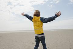 Stock Photo of Germany, St.Peter-Ording, North Sea, Boy (8-9) in rain coat standing on beach,