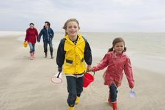 Germany, St. Peter-Ording, North Sea, Children (6-9) with parents walking on Stock Photos