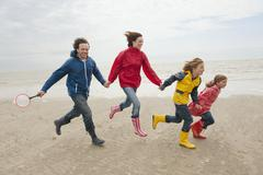 Stock Photo of Germany, St. Peter-Ording, North Sea, Family holding hands and running on beach