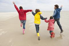Germany, St. Peter-Ording, North Sea, Family holding hands and running on beach - stock photo