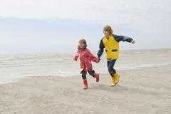 Germany, St. Peter-Ording, North Sea, Boy and girl (6-9) holding hands and Stock Photos