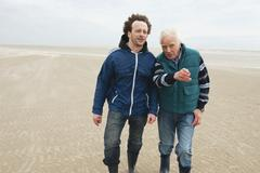 Germany, St. Peter-Ording, North Sea, Senior man and son walking on beach Stock Photos