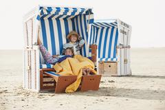 Germany, St.Peter-Ording, North Sea, Children (6-9) resting on hooded beach Stock Photos