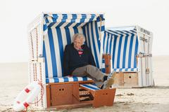 Germany, St. Peter-Ording, North Sea, Senior man relaxing on hooded beach chair - stock photo