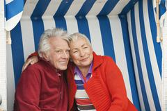Germany, North Sea, St.Peter-Ording, Senior couple sitting on hooded beach chair Stock Photos