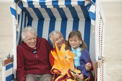Germany, St. Peter-Ording, North Sea, Girl (6-7) sitting with grandparents on Stock Photos