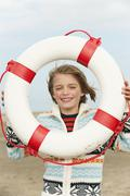 Germany, North Sea, St.Peter-Ording, Boy (8-9) holding life saver at beach, Stock Photos