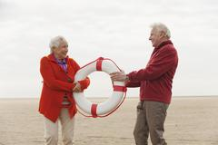 Germany, St. Peter-Ording, North Sea, Senior couple holding lifesaver on beach - stock photo