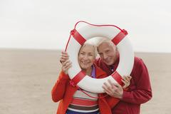 Germany, St Peter-Ording, North Sea, Senior couple looking through lifesaver, Stock Photos