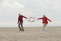 Germany, St Peter-Ording, North Sea, Senior couple pulling lifesaver on beach - stock photo