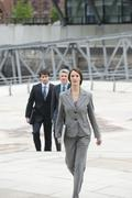 Germany, Hamburg, Businesswoman walking with business people in background Stock Photos