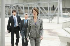 Germany, Hamburg, Businesswoman walking with business people in background - stock photo