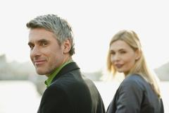 Stock Photo of Germany, Hamburg, Businessman smiling with woman in background