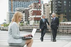 Germany, Hamburg, Businesswoman using laptop with business man in background Stock Photos