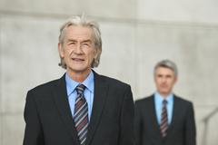 Germany, Hamburg, Businessmen, senior man smiling in foreground - stock photo