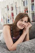 Germany, Hamburg, Woman resting on sofa, smiling - stock photo