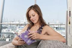 Germany, Hamburg, Woman reading book with harbor in background Stock Photos