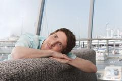 Germany, Hamburg, Man sitting on sofa and looking up Stock Photos