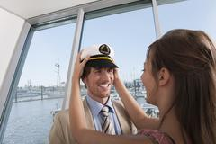 Stock Photo of Germany, Hamburg, Woman wearing sailor's cap to man, smiling