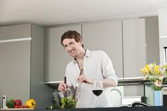 Germany, Hamburg, Man in kitchen preparing salad Stock Photos