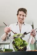 Germany, Hamburg, Man in kitchen mixing vegetable Stock Photos