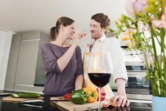 Germany, Hamburg, Woman feeding slice of capsicum to man - stock photo