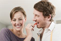Germany, Hamburg, Woman feeding slice of capsicum to man Stock Photos