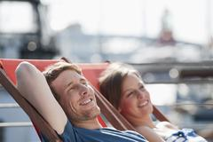 Germany, Hamburg, Couple relaxing in deck chair looking away, smiling Stock Photos