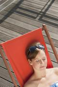 Germany, Hamburg, Woman resting on deck chair Stock Photos