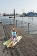 Stock Photo of Germany, Hamburg, Woman sitting on sun deck and listening to music