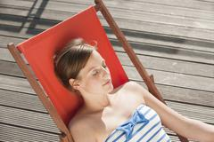 Germany, Hamburg, Woman resting on deck chair - stock photo